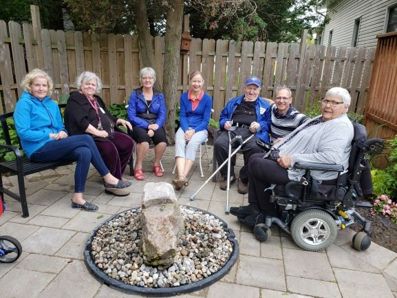 Day Hospice volunteers and clients enjoying the new outdoor patio and fountain